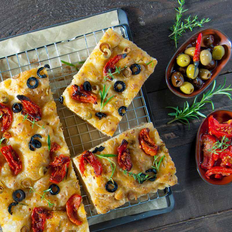 foto van focaccia met zongedroogde tomaten en zwarte olijven