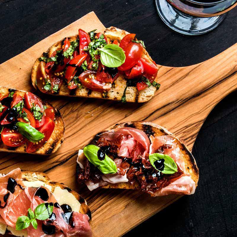 foto van geroosterd brood met knoflook, gorgonzola, parmaham en gedroogde tomaten